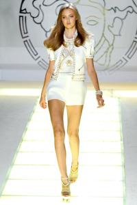 Giacca, top e shorts bianchi con borchie dorate